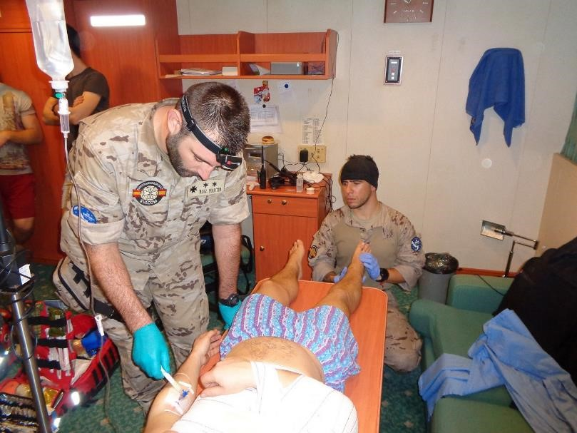 The frigate 'Victoria' provides medical assistance to a crew member of a merchant ship